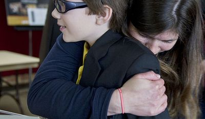Jill Johnston hugs her son Forrest, 11, after he won first place in the Junior division of the National Trumpet Competition on Sunday, March 18, 2012 at George Mason University in Fairfax, Va. Forrest says he was happy to make it to the finals and can't believe he actually won. (Barbara L. Salisbury/The Washington Times)