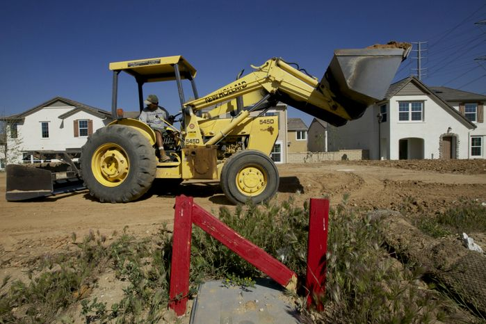 A skid-steer-loader flattens the land for a new single-family detached home being built by Lennar at the Aria at West Creek development in Santa Clarita, Calif., on Thursday, March 15, 2012. (AP Photo/Damian Dovarganes)