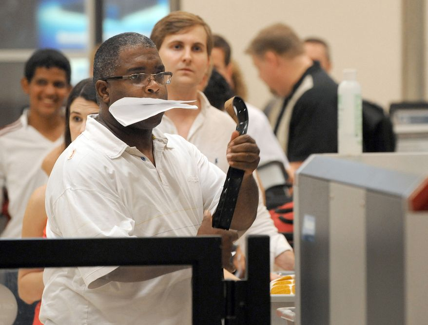 ** FILE ** Airline passengers go through the Transportation Security Administration security checkpoint at Hartsfield-Jackson Atlanta International Airport in Atlanta on Aug. 3, 2011. (Associated Press)