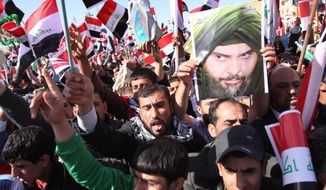 Followers of Shiite cleric Muqtada al-Sadr chant anti-Iraqi government slogans and wave Iraqi flags during a protest March 19, 2012, in Basra, Iraq's second-largest city, 550 kilometers (340 miles) southeast of Baghdad. Followers of the anti-American Shiite cleric Muqtada al-Sadr, seen on the poster, are demanding better living conditions in Iraq on the ninth anniversary of the U.S.-led invasion of their country. (Associated Press)