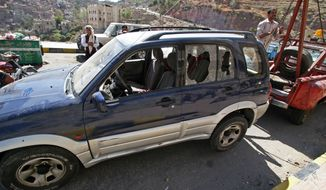A damaged vehicle said to belong to an American teacher shot by two motorcycle gunmen is towed away in Taiz, Yemen, on Sunday, March 18, 2012. (AP Photo/Anees Mahyoub)