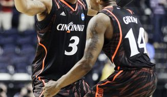 Cincinnati's Dion Dixon (3) and Ge'Lawn Guyn (14) celebrate after defeating Florida State 62-56 in the third-round NCAA college basketball tournament game on Sunday, March 18, 2012, in Nashville, Tenn. (AP Photo/Mark Humphrey)