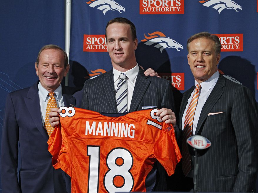 New Denver Broncos quarterback Peyton Manning, center, is flanked by Broncos owner Pat Bowlin, left, and vice president John Elway during a news conference at the Broncos headquarters in Englewood, Colo., on Tuesday, March 20, 2012. (AP Photo/Ed Andrieski)