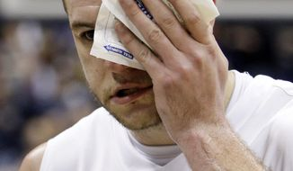** FILE ** In this Dec. 10, 2011 file photo, Xavier center Kenny Frease covers his swollen eye as he walks off the floor after a fight at the end of Xavier's 76-53 win over Cincinnati in an NCAA basketball game. Three months later, Xavier and Cincinnati have reached the round of 16 in the NCAA tournament while refurbishing their images. (AP Photo/Al Behrman, File)