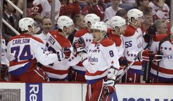 Washington Capitals' Alex Ovechkin (8) is congratulated by his teammates after scoring during the first period of an NHL hockey game against the Detroit Red Wings in Detroit, Monday, March 19, 2012. (AP Photo/Carlos Osorio)