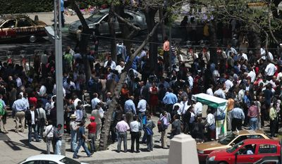 Workers and residents gather at the Angel de la Independencia Square after evacuating buildings following a long, strong earthquake in Mexico City on Tuesday, March 20, 2012. (AP Photo/Dario Lopez-Mills)