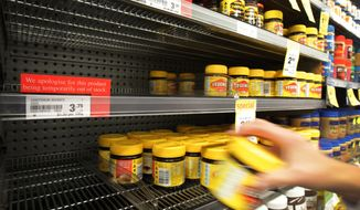 A customer takes a jar of Vegemite from the shelf next to an empty section where Marmite should be stocked in a supermarket in Auckland, New Zealand, on Tuesday, March 20, 2012. (AP Photo/New Zealand Herald, Sarah Ivey)