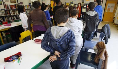 Pupils of the Georges Brassens College in Paris and their head teacher, Marianne Dodinet (center), hold a minute of silence on Tuesday, March 20, 2012, the day after a gunman on a motorbike opened fire at a Jewish school in Toulouse, France, and killed a rabbi, his two young sons and a third child. (AP Photo/Francois Mori)