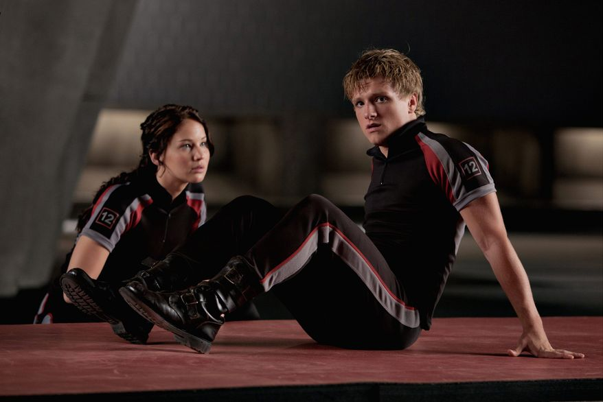 Pitted against each other in a showdown to the death, Katniss (Jennifer Lawrence) and Peeta (Josh Hutcherson) are encouraged to present themselves as lovers. (Lionsgate via Associated Press)
