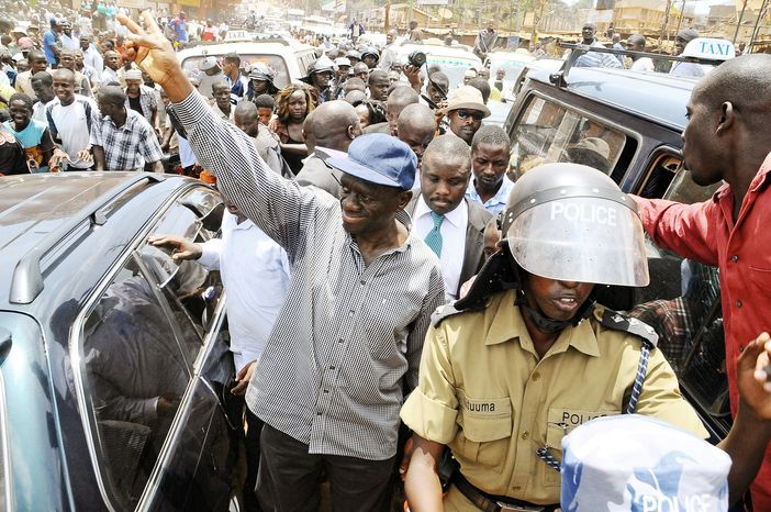 Kizza Besigye, a Ugandan opposition leader with the Forum for Democratic Change, gestures the party sign before being arrested Wednesday for holding a rally in the capital city
