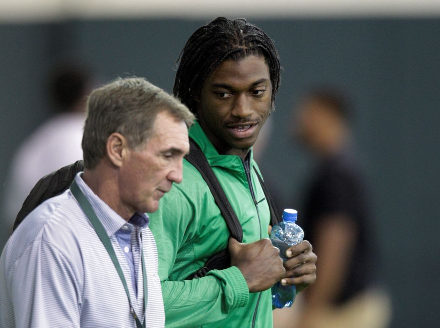 Washington Redskins coach Mike Shanahan (left) speaks Wednesday with Heisman Trophy-winning quarterback Robert Griffin III at Baylor's pro day in Waco, Texas. (Associated Press)