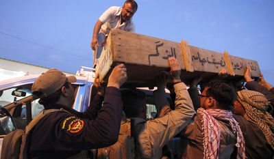 Family members of Ahmed Mohammed, 34, who was killed in a car bombing, load his coffin onto a vehicle before burial in Najaf, Iraq, on Tuesday, March 20, 2012. (AP Photo/Alaa al-Marjani)