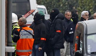Police officers and firefighters stand near a building in Toulouse, France, Wednesday, March 21, 2012, where a suspect in the shooting at he Ozar Hatorah Jewish school has been spotted. (AP Photo/Remy de la Mauviniere)