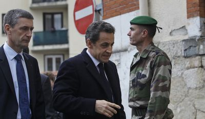 France's President Nicolas Sarkozy, center, with Frederic Pechenard, director of the French police, left, arrives to meet soldiers and police officers close to the apartment building where a suspect in the shooting at the Ozar Hatorah Jewish school is barricaded in Toulouse, Southern France, Wednesday, March 21, 2012. (AP Photo/Christophe Ena)