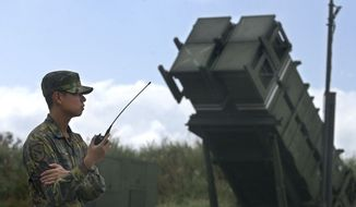 ** FILE ** A Taiwanese soldier stands at attention in front of a Patriot missile air defense system near the northern coastal town of Wanli, Taiwan, in October 2004. (AP Photo/Wally Santana)
