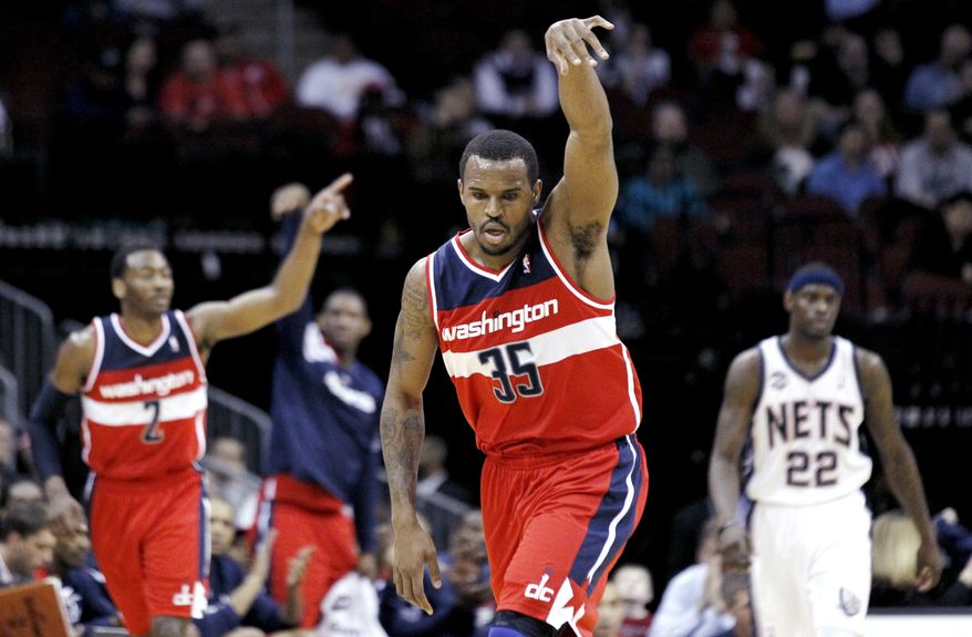 Washington Wizards' Trevor Booker, center, reacts after hitting a 3-pointer against the New Jersey Nets in the first quarter of an NBA basketball game, Wednesday, March 21, 2012, in Newark, N.J. (AP Photo/Julio Cortez)