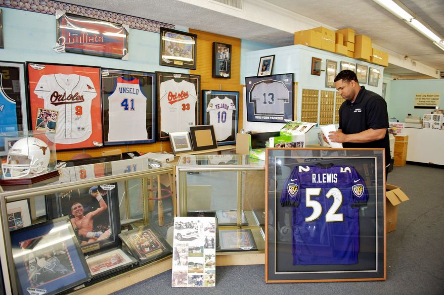 """Robbie Davis Jr. straightens the counter at the sports-memorabilia shop Robbie's First Base, which he owns with his father in Lutherville, Md. The store is featured in """"Ball Boys,"""" premiering Saturday on ABC. (Mary F. Calvert/Special to The Washington Times)"""