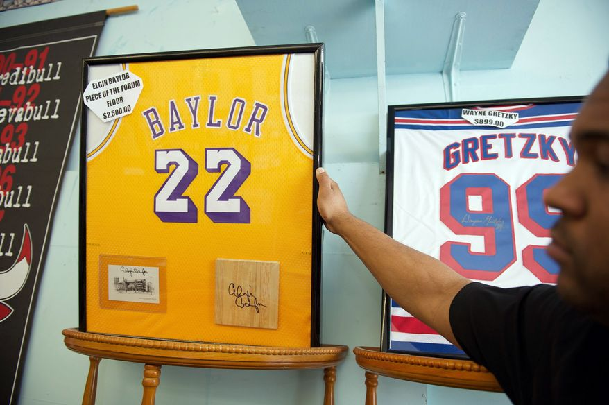 "Robbie Davis Jr., 33, points out a Los Angeles Lakers Elgin Baylor jersey and piece of the Forum floor at the sports memorabilia shop, ""Robbie's First Base"" in Lutherville, Md. Robbie Davis Jr., 33, and his dad, Robbie Davis Sr. 60 star in a reality show called ""Ball Boys"" that will debut Saturday at 3 p.m. on ABC. (Mary F. Calvert/Special to The Washington Times)"