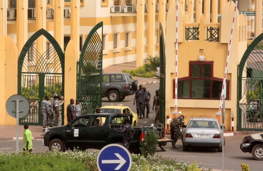 Soldiers gather in Bamako, Mali, on Thursday at an entrance to the compound containing government ministries after taking power in a coup, Drunken soldiers looted Mali's presidential palace hours after they declared a coup on Thursday, suspending the constitution and dissolving the institutions of one of the few established democracies in this troubled corner of Africa. (Associated Press)