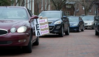 """A driver holds a """"Taxed Enough Already"""" sign out of his car as he and a handful of other cars drive around the State House in Annapolis, Md., on Thursday, March 22, 2012, honking their horns in protest of new and increased taxes in the state of Maryland. At least two drivers were ticketed for illegal use of horn, a $60 fine. (Barbara L. Salisbury/The Washington Times)"""