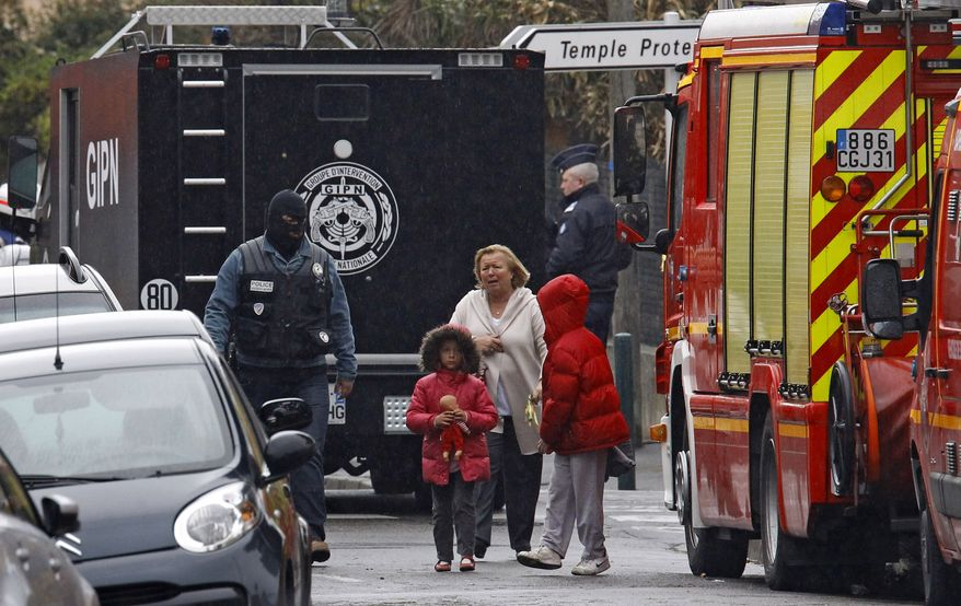 A woman and children are escorted by a police officer near a building where the chief suspect in an al Qaeda-linked killing spree was holed up in an apartment in Toulouse, France, Thursday March 22, 2012. (AP Photo/Remy de la Mauviniere)