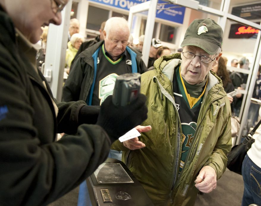 John Wood, right, hands his ticket to an attendant as he and friend Mel Murray, behind, enter the John Labatt Centre to watch the hometown London Knights play hockey against the visiting Oshawa Generals in London, Ontario, Canada on Friday March 2, 2012.  The hockey fans have been season ticket holders of the junior hockey club for the past 8 years. (Craig Glover/Special to The Washington Times)