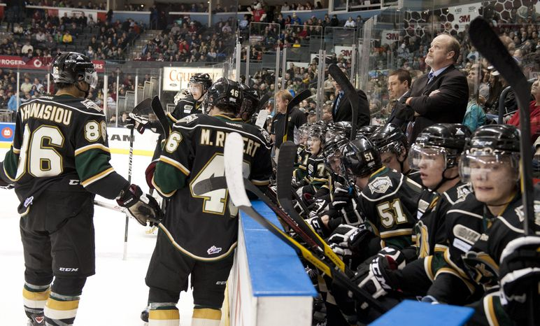 London Knights head coach Mark Hunter, right, glances up at the scoreboard from the bench during their junior hockey game against the Oshawa Generals at the John Labatt Centre in London, Ontario, Canada on Friday March 2, 2012.  Mark took over the role after his brother, Dale Hunter, became head coach of the Washington Capitals. (Craig Glover/Special to The Washington Times)