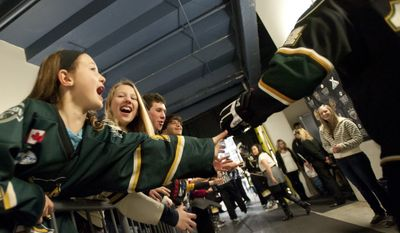 Cassie Brock, 13, laughs as her cousin, Kylie Brock, 9, left, reaches out to high five London Knights defenseman Tommy Hughes as he walks through the home players' tunnel at the John Labatt Centre in London, Ontario, Canada on Friday March 2, 2012.  (Craig Glover/Special to The Washington Times)