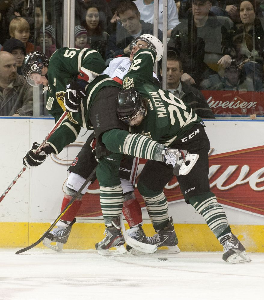 Ottawa 67's winger Shane Prince, middle, is sandwiched into the boards by London Knights forwards Austin Watson, left, and Colin Martin, right, during their junior hockey game at the John Labatt Centre in London, Ontario, Canada on Saturday March 3, 2012. (Craig Glover/Special to The Washington Times)
