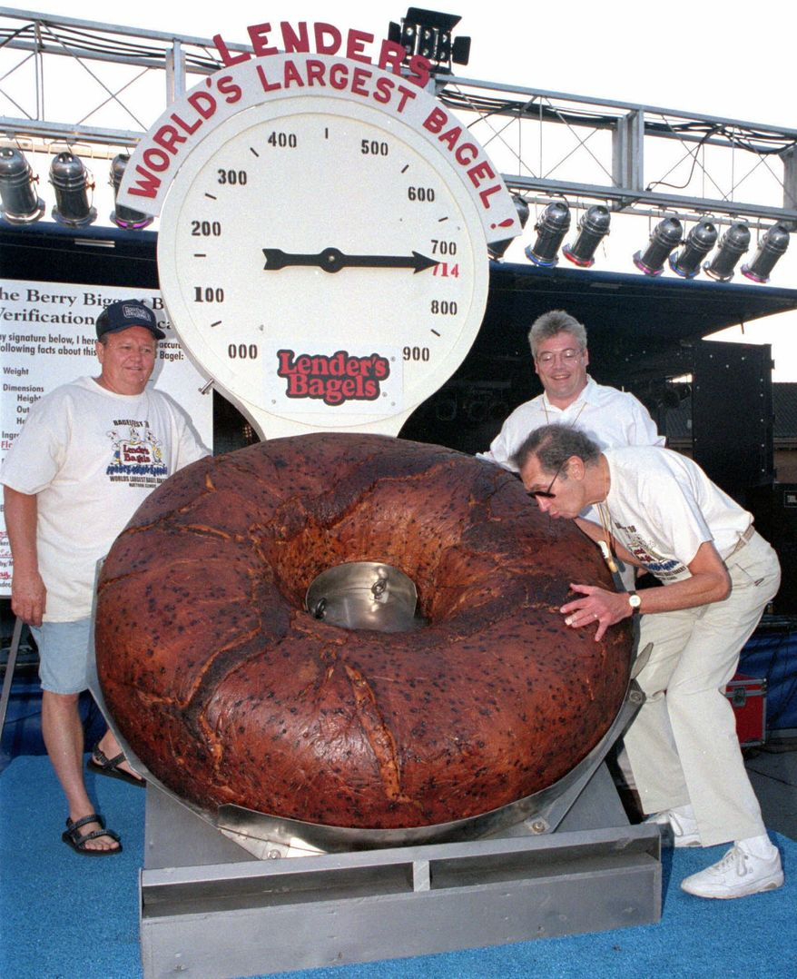 **FILE** Murray Lender kisses the world's largest bagel while baker Larry Wilkerson (left) and Lender's Bagel Bakery manager Jim Cudahy watch on July 24, 1998, after the weight of the bagel was revealed during Bagelfest in Mattoon, Ill. (Associated Press/Journal Gazette)