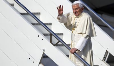 Pope Benedict XVI waves March 23, 2012, as he boards a plane at Rome's Fiumicino Airport to begin a six-day visit to Mexico and Cuba. (Associated Press)