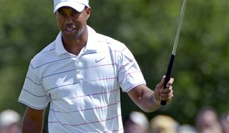 Tiger Woods waves his club to the gallery after a birdie putt on the sixth hole during the second round of the Arnold Palmer Invitational at Bay Hill, Friday, March 23, 2012, in Orlando, Fla. (AP Photo/Phelan M. Ebenhack)