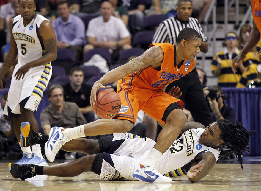 Florida's Bradley Beal (23) moves past Marquette's Jae Crowder (32) as Marquette's Junior Cadougan watches during the first half of an NCAA men's college basketball tournament West Regional semifinal on Thursday, March 22, 2012, in Phoenix. (AP Photo/Chris Carlson)