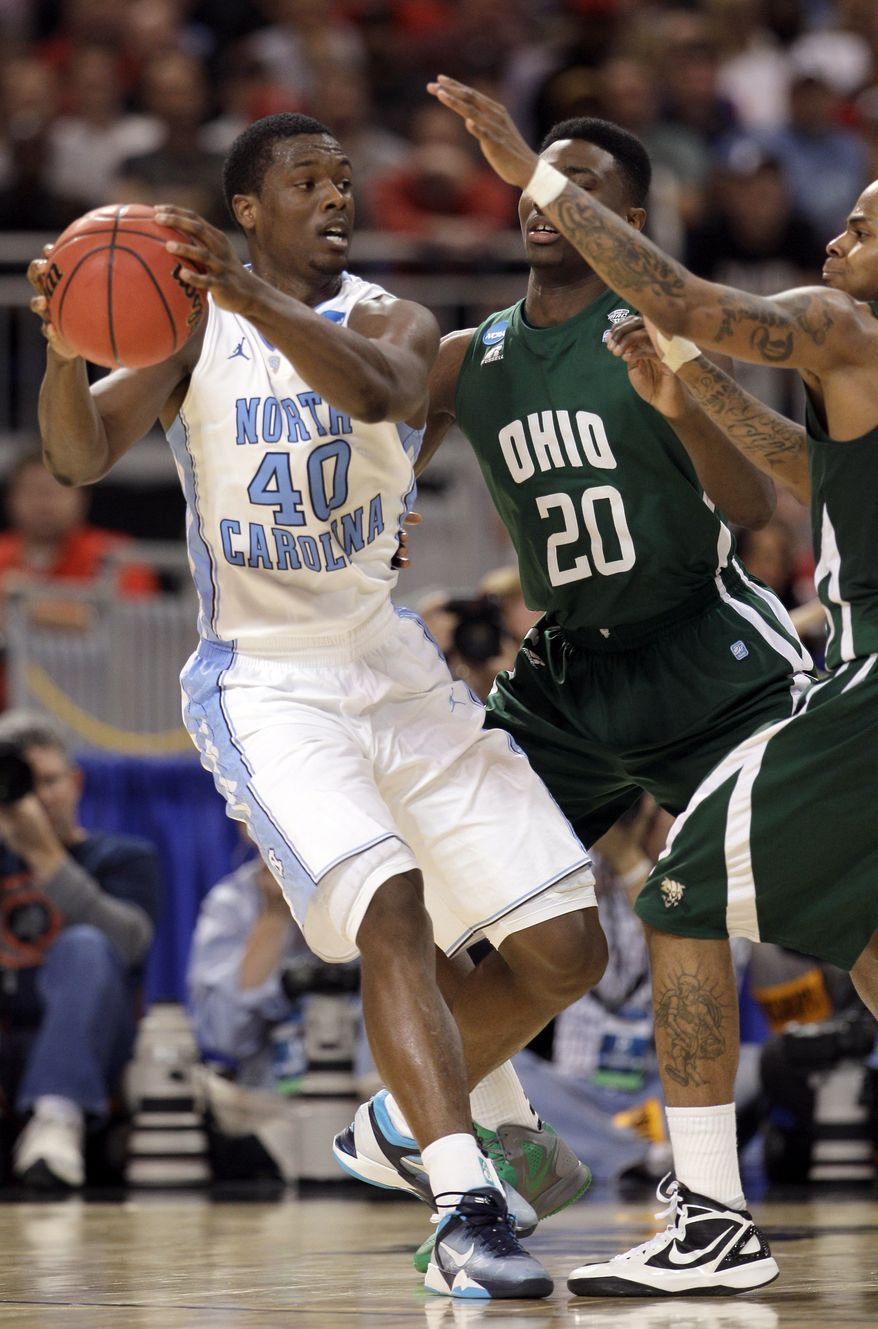 North Carolina Tar Heels' Harrison Barnes is defended by Ohio Bobcats' Ricardo Johnson, center, and D.J. Cooper during the second half of an NCAA tournament Midwest Regional game Friday, March 23, 2012, in St. Louis. (AP Photo/Charlie Riedel)