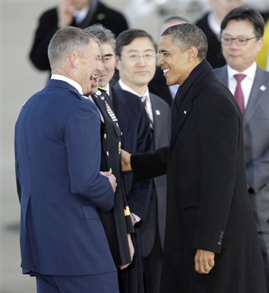President Barack Obama is greeted by Col. Patrick McKenzie, left, Commander, 51st Fighter, upon arrival at Osan Air Base to attend the Nuclear Security Summit, in Osan, south of Seoul, South Korea, Sunday, March 25, 2012. (AP Photo/Lee Jin-man)