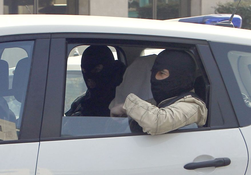 An unidentified man with his head covered, believed to be Abdelkader Merah or his companion, sits between masked police officers as they head to the French police's anti-terrorist headquarters in Levallois-Perret, outside Paris, Saturday, March 24, 2012. Merah's brother, Mohamed Merah is blamed for a series of deadly shootings which have shocked France and upended the country's presidential race. (AP Photo/Christophe Ena)