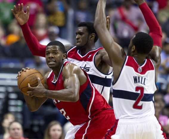 Atlanta Hawks' Joe Johnson tries to keep the ball away from Washington Wizards defenders Chris Singleton, center, and John Wall during the closing seconds of the second half  Saturday, March 24, 2012 in Washington. The Hawks won 95-92. (AP Photo/Evan Vucci)