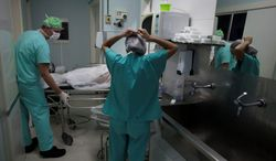 ** FILE ** A doctor wheels a patient out of an operating room at Santa Casa de Misericordia Hospital in Rio de Janeiro. (Associated Press)