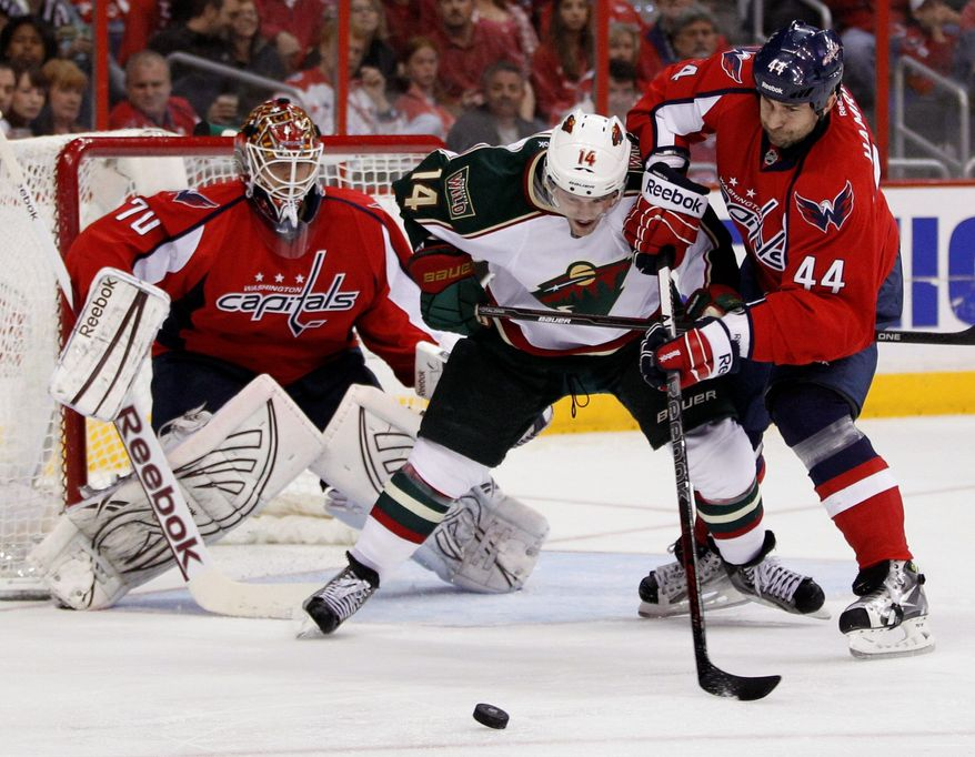 Braden Holtby turned aside 28 shots in Washington's 3-0 win over Minnesota that lifted the Capitals into eighth place in the Eastern Conference. Romank Hamrlik (44) helped by keeping Darroll Powe from the puck. (Associated Press)