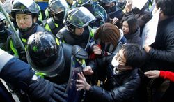 Demonstrators scuffle with riot police during a protest in downtown Seoul on Sunday. Both pro and anti-nuclear protesters turned out on the day before world leaders met for the start of a two-day Nuclear Security Summit.
