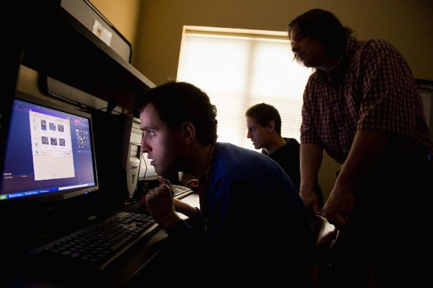 Brian and James edit their photographs of the Washington cherry blossoms with the help of staff member Craig Pardini in the computer lab at the Community Services for Autistic Adults and Children in Montgomery Village last week. (Andrew Harnik/The Washington Times)