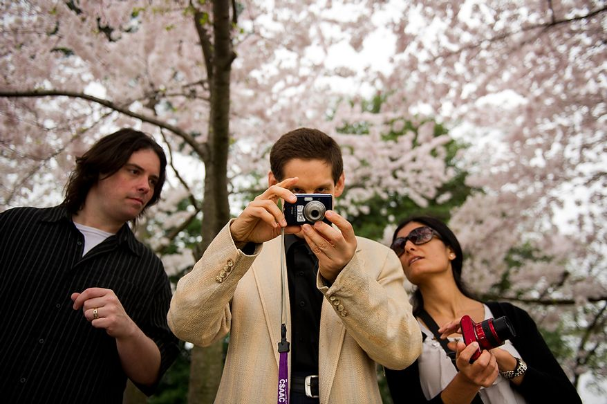"""Autistic adult James L., center, with Community Services for Autistic Adults and Children, based in Montgomery Village, Md., is accompanied by staff members Craig Pardini, left, and Dide Cimen, right, as he takes photographs of the Cherry Blossoms along the Tidal Basin, Washington, D.C., Wednesday, March 21, 2012. The """"InFocus Project†is a way for adults with autism to develop forms of self expression and social skills while producing work that has been featured in art shows, given to donors to C.S.A.A.C., and sold on an online store. (Andrew Harnik/The Washington Times)"""