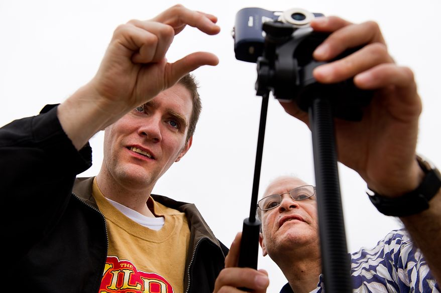"Staff member Renee Gonzales, right, with Community Services for Autistic Adults and Children, based in Montgomery Village, Md., helps autistic adult Matt D., left, take photographs of the Cherry Blossoms along the Tidal Basin, Washington, D.C., Wednesday, March 21, 2012. The ""InFocus Project†is a way for adults with autism to develop forms of self expression and social skills while producing work that has been featured in art shows, given to donors to C.S.A.A.C., and sold on an online store. (Andrew Harnik/The Washington Times)"