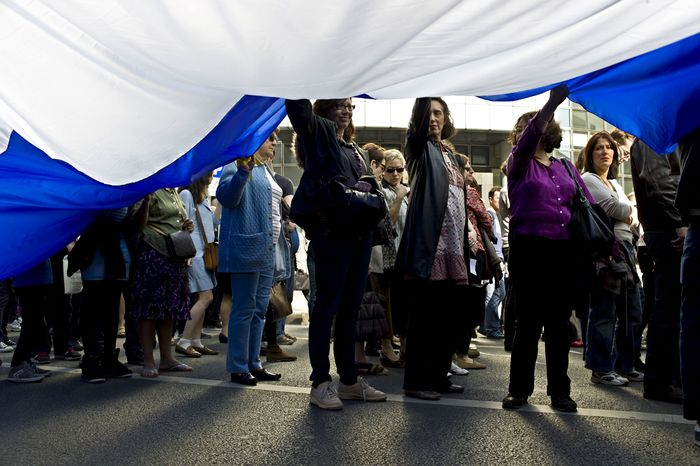 Demonstrators carry a giant French flag as they attend a march in Paris on Sunday, March 25, 2012, in memory of the seven victims of gunman Mohamed Merah. (AP Photo/Thibault Camus)
