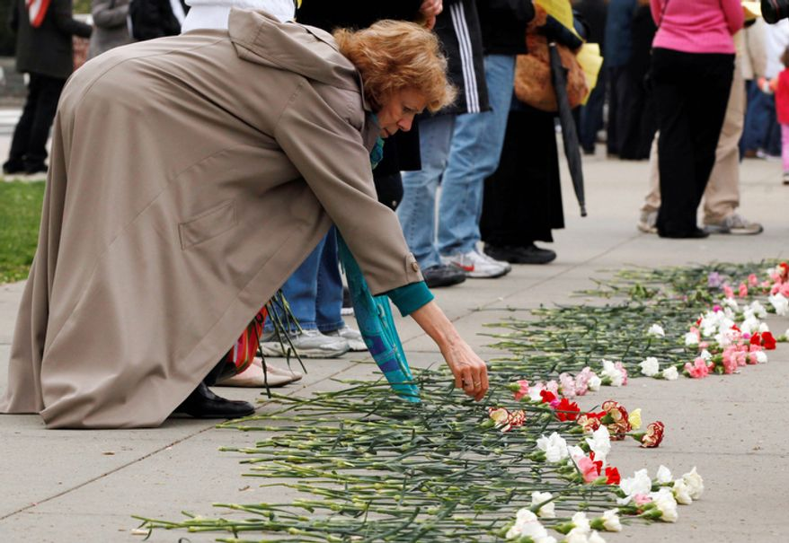 "A woman adds a flower to the sidewalk around the Supreme Court as part of ""Encircle the Court in Prayer,"" event led by Christian faith organizations. (AP Photo/Jacquelyn Martin)"