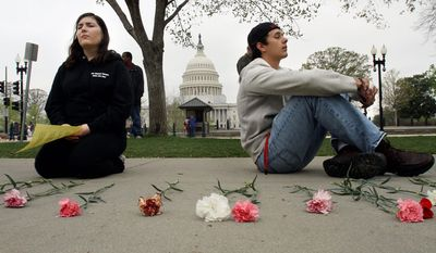 """Gretchen Midgley, left, and Jonathan McGee, both students at Catholic University, pray with the U.S. Capitol in the background during """"Encircle the Court in Prayer,"""" an event led by Christian faith organizations. (AP Photo/Jacquelyn Martin)"""