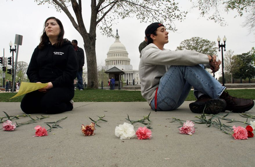 "Gretchen Midgley, left, and Jonathan McGee, both students at Catholic University, pray with the U.S. Capitol in the background during ""Encircle the Court in Prayer,"" an event led by Christian faith organizations. (AP Photo/Jacquelyn Martin)"