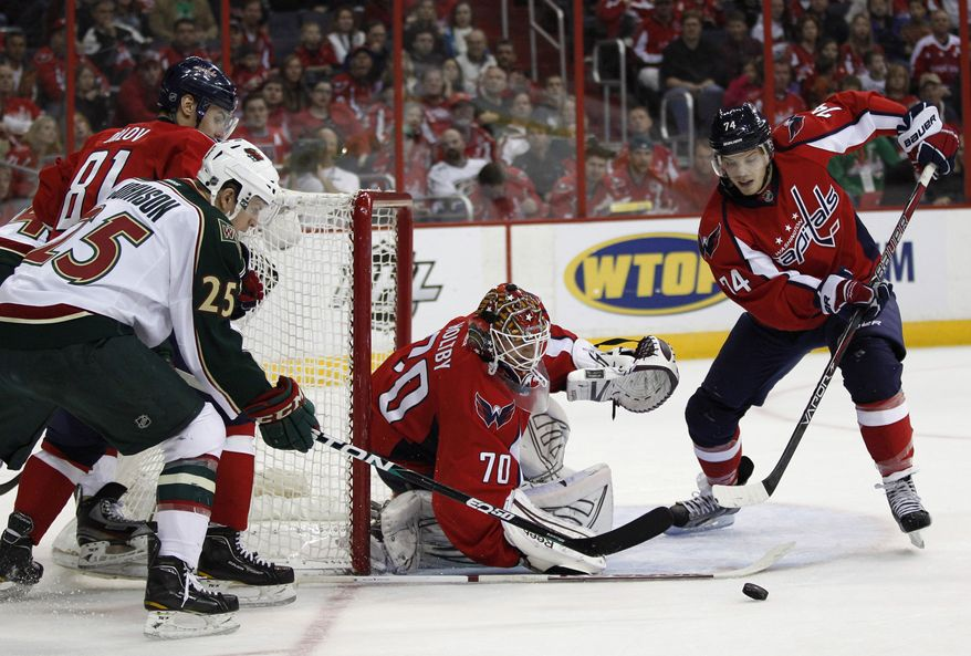 Washington Capitals goalie Braden Holtby (70) makes a save against Minnesota Wild right wing Nick Johnson (25) during the first period of an NHL hockey game Sunday, March 25, 2012, in Washington. From left are Washington Capitals defenseman Dmitry Orlov, Johnson, Holtby, and Capitals defenseman John Carlson. (AP Photo/Evan Vucci)
