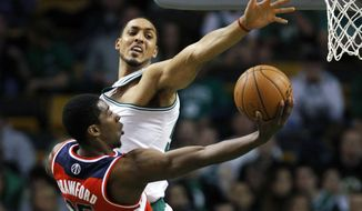 Washington Wizards' Jordan Crawford (15) shoots against Boston Celtics' Ryan Hollins in the second quarter of an NBA basketball game in Boston, Sunday, March 25, 2012. (AP Photo/Michael Dwyer)