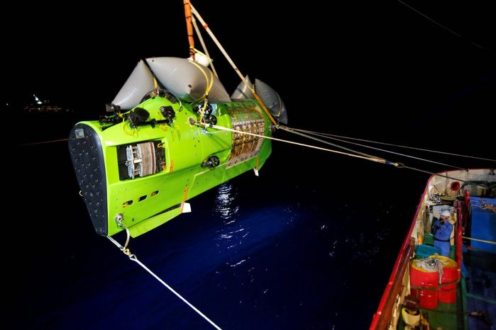The Deepsea Challenger submersible with James Cameron inside is moved into place to begin its descent 7 miles below the surface of the Pacific Ocean to the Mariana Trench. The movie director
